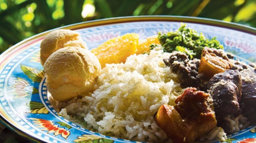 Feijoada with oranges, kale, farofa, rice and pao de queijo